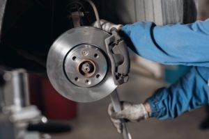 Kfz-Mechaniker wechselt Bremsen aus.