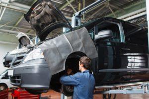 Kfz-Mechaniker in Werkstatt wechselt Bremsen.