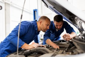 Kfz-Mechaniker kontrollieren den Motor eines Autos in der Werkstatt.