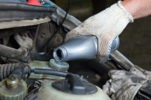 KFZ-Mechaniker befüllt Auto mit Bremsflüssigkeit.
