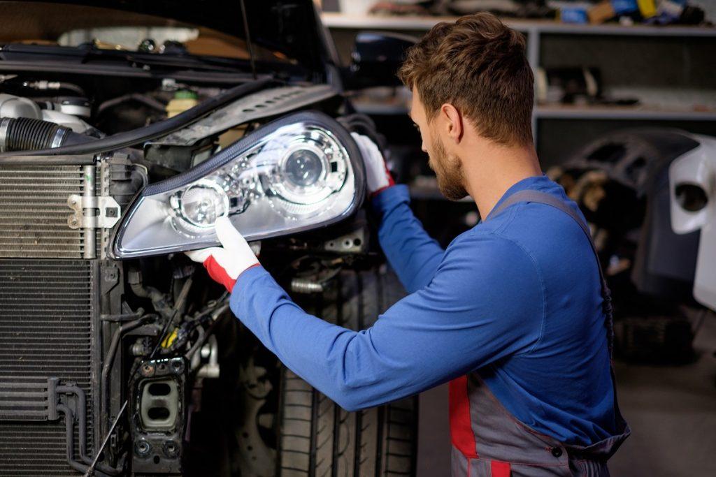 Mechaniker der Scheinwerfer austauscht | Autoreparaturen.de